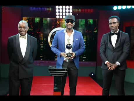 Busy Signal (centre) poses with his Dancehall Artiste of the Decade award, alongside IRAWMA organiser Ephraim Martin (left) and host Winford Williams. Photo at right: Stranger Cole receives one of the Icon awards at the 38th staging of the IRAWMA event. Looking on are organiser Ephraim Martin (left) and host Winford Williams.