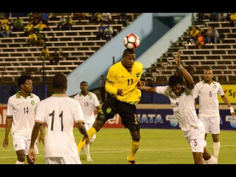 Reggae Boy Corey Burke (centre) outjumps the Suriname defenders during a Caribbean Cup qualifier at the National Stadium in 2016.