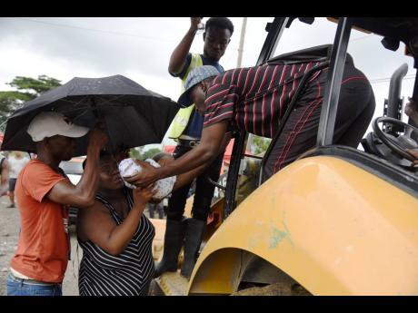 Sheryl Baker gently takes her four-day-old baby boy after piggybacking on this tractor to get across the heavy water passing through Font Hill, St Thomas.