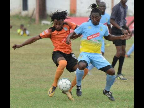 FILE Waterhouse's Keammar Daley (right) tries to evade a tackle from Tivoli Gardens' Tevin Shaw during their National Premier League match at the Edward Seaga Sports Complex on Sunday, March 17, 2019.