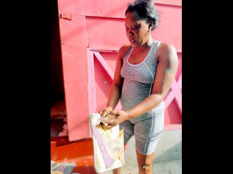 Tanesha Rodriques, a resident of Greenwich Town,  St Andrew looks at school supplies for her daughter, which were damaged due to flood waters leaving Marcus Garvey Drive and entering her home.