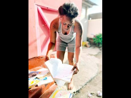 Tanesha Rodriques looks at school supplies for her daughter, which were damaged due to flood waters leaving Marcus Garvey Drive and entering her home.