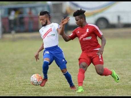 In this  May 2017 file photo, Portmore's Maalique Foster (left) shrugs off a challenge from UWI's Allando Brown during their National Premier League semi- final match at the UWI Mona Bowl.