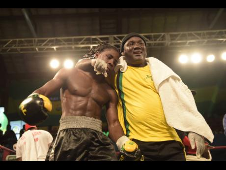 Coach Carl Grant congratulates Bruising Gym boxer Richard 'Frog' Holmes after a win over Frank Cotroni in the Wray and Nephew 'Contender' boxing series in  June  2017.