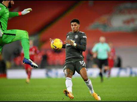 Liverpool's goalkeeper Alisson clears the ball away from Manchester United's Marcus Rashford during their English Premier League match at Anfield Stadium, Liverpool, England, yesterday.