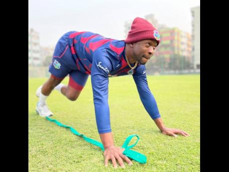 West Indies' fast bowler Kemar Roach stretches during a training session in Bangladesh yesterday.