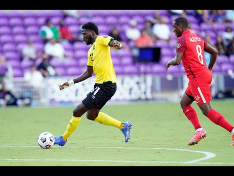 Jamaica's Shamar Nicholson (left) moves  away from Guadeloupe's midfielder Edwing Malpon  during the first half of  their Concacaf  Gold Cup Group C match last Friday. Jamaica won 2-1.